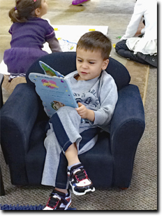 boy sitting while reading a book